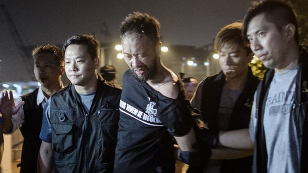 Civic Party member Ken Tsang, one of Hong Kong's pro-democracy political groups, is taken away by policemen, before being allegedly beaten up by police forces