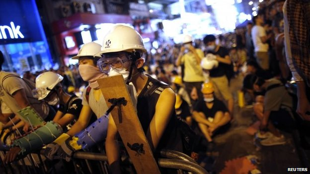 Pro-democracy protesters stand by a barricade as they prepare for a confrontation with riot police at the Mongkok shopping district of Hong Kong, 19 October 2014