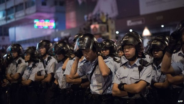 A policeman puts on his helmet during a stand-off with pro-democracy protesters in the Mong Kok district of Hong Kong, 19 October 2014