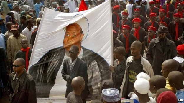 Black-shirted followers of a Sha Muslim sect carry a banner depicting their leader Ibrahim Zakzaky  on 10 February 2005 in the northern Nigerian city of Kano