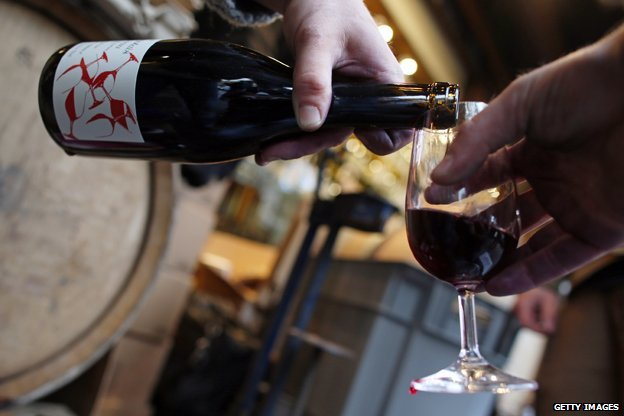 Wine is poured from a bottle of Beaujolais Nouveau
