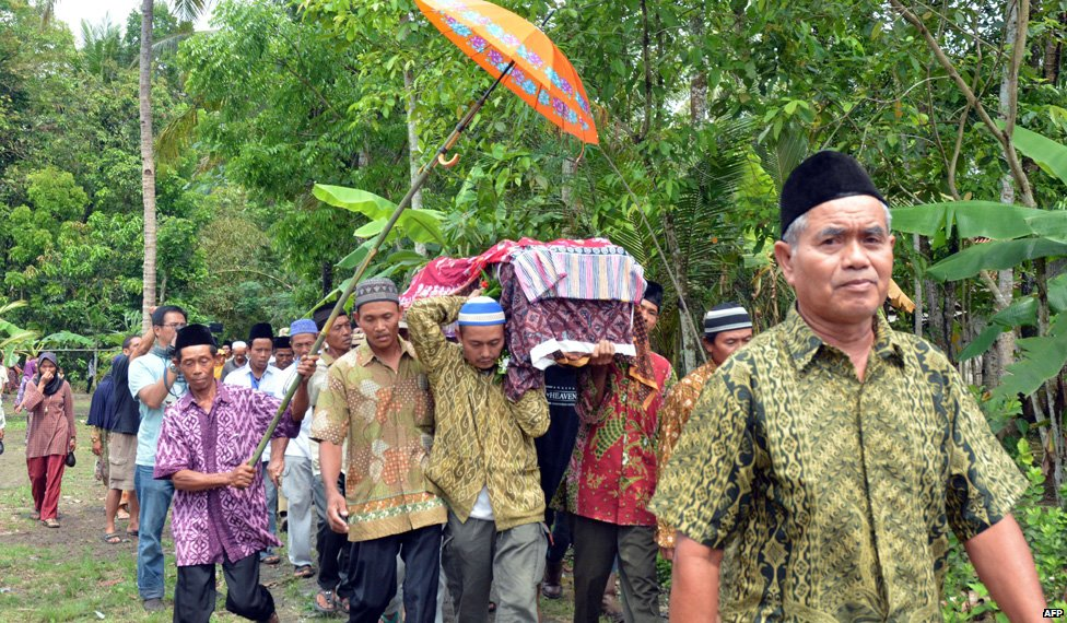 Relatives and villagers carry the coffin of Sumarti Ningsih