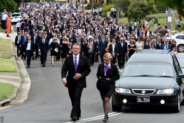 A large procession of mourners walk through the streets of Macksville