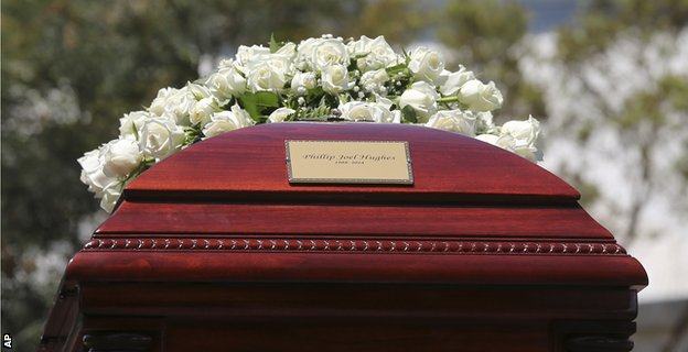 The coffin was topped with white flowers