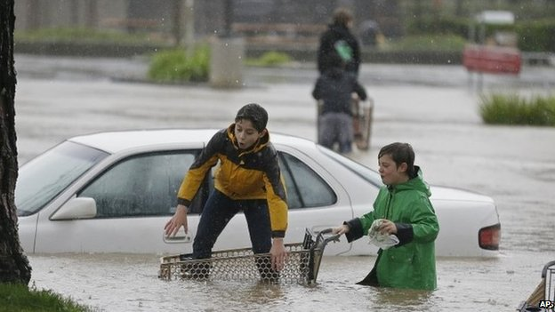 Aidan Perez, left, 12, and Christopher Dow, right, 11, use a shopping cart to get around the flooded parking lot of a shopping center Thursday, Dec. 11, 2014, in Healdsburg, California 11December 2014