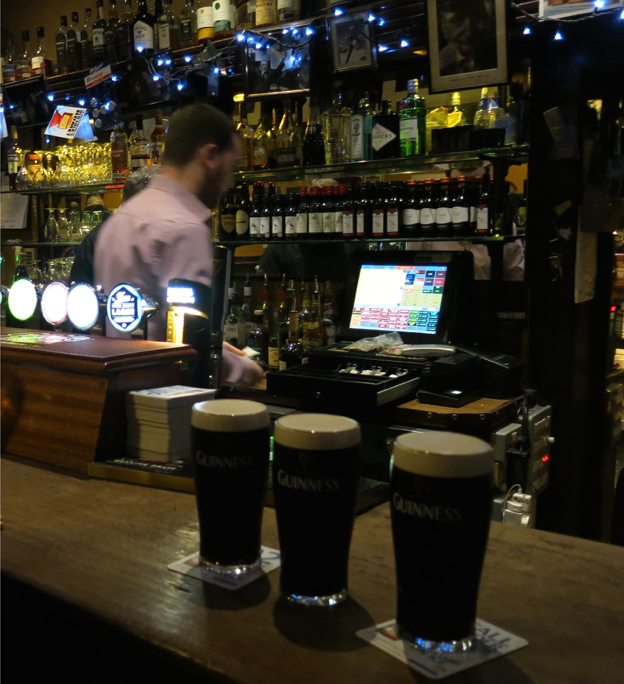 Three pints of Guinness on a bar