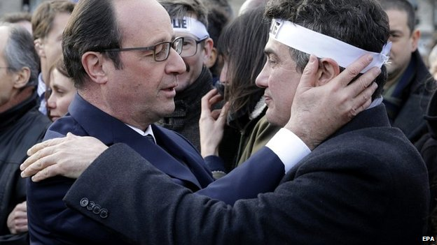 French President Francois Hollande hugs Charlie Hebdo journalist Patrick Pelloux during the unity march in the streets of Paris - 11 January 2015
