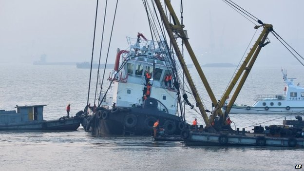 "Rescuers approach the lifted wreckage of capsized tug boat ""Wanshenzhou 67"" on the Yangtze River near Jingjiang, east China's Jiangsu Province, 17 January 2015"
