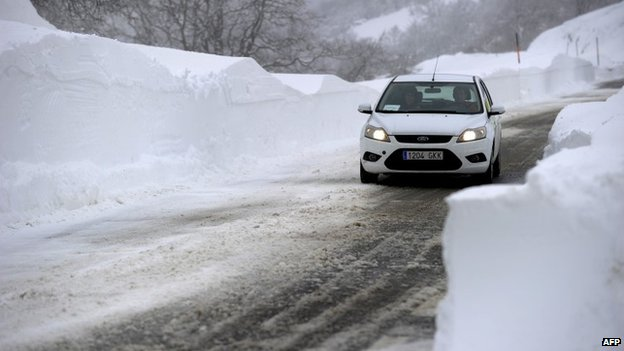 A car drives in along a snow covered road near the village of Uharte Arakil in Navarre following heavy snow storms in northern Spain on 4 February, 2015.