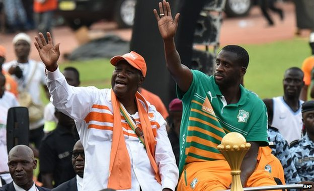 Ivorian President Alassane Ouattara and Ivory Coast captain Yaya Toure wave at the crowd
