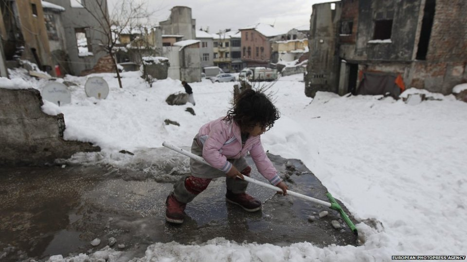 A Syrian refugee child clears snowin Istanbul, Turkey