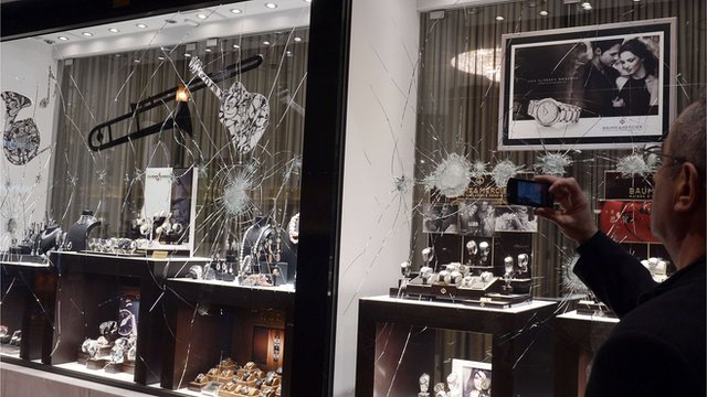A man takes a picture of a broken shop window of a jewellery shop, which was damaged by demonstrators in Athens on 26 February