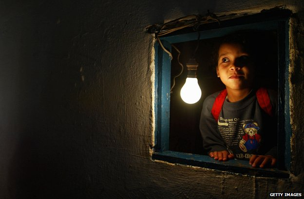 A girl in Morocco next to a newly-installed lightbulb