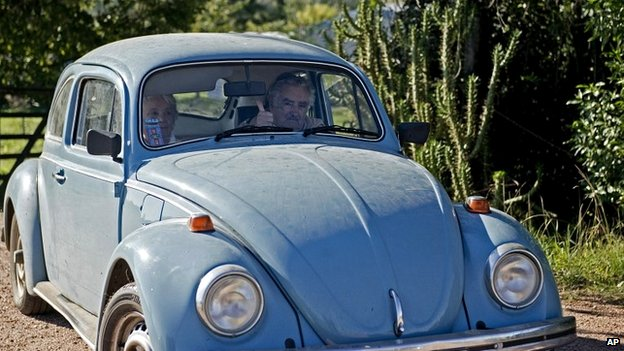 Uruguay's President Jose Mujica flashes a thumbs up as he and and his wife leave their home on the outskirts of Montevideo in their famous VW Beetle - 2 May 2014
