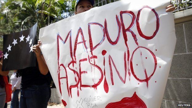 Opposition supporter holds a sign during a gathering to protest the death of an student in Tachira State, in Caracas