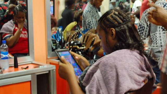 A customer reading a tablet whilst having her hair done in Bruno's Place hair salon in Ikeja Mall in Lagos, Nigeria