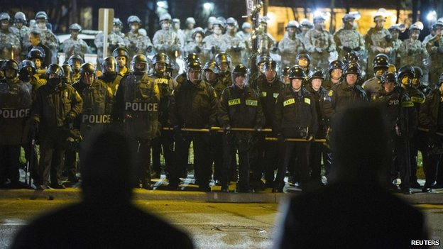 Protesters stare at a line of police officers and National Guard soldiers during a protest to demand justice for the killing of 18-year-old Michael Brown