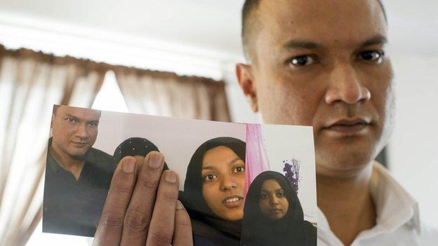 Mohammad Uddin holding photos of daughter Sharmeena Begum