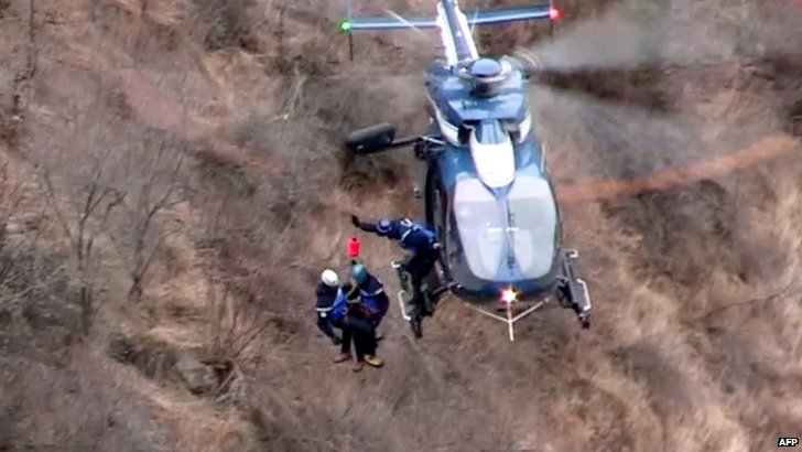 Search and rescue teams being lowered from a helicopter to the crash scene