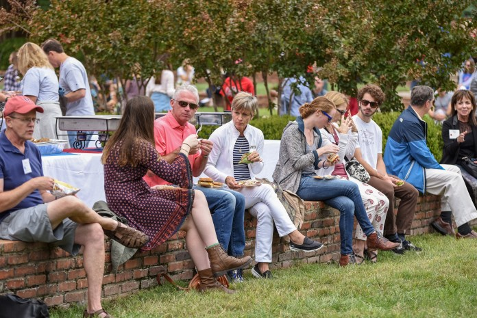 Parents sit on the lawn and enjoy a meal at Parents and Family Weekend.