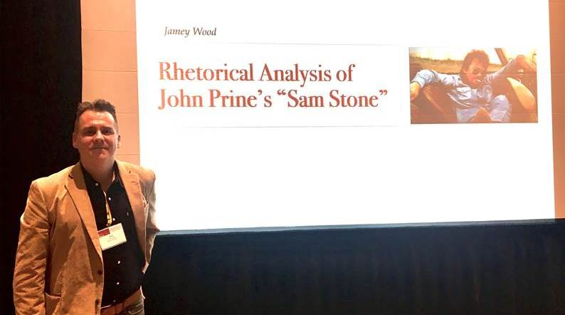 Wood standing in front of his presentation at the February conference