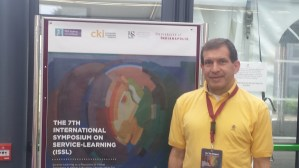 Stewart in front of a sign at the International Symposium.