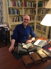 Dr. Douglas Murray poses with a collection of books inside Chawton