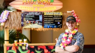 Nathan Fink stands in front of his Maui Wowie stand on belmont's campus,.