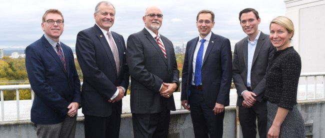 A group of Massey faculty standing on a balcony with the consulate of Belgium