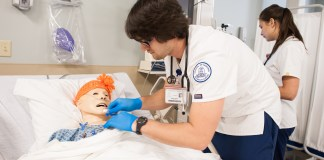 A nursing student works along a simulator on Belmont's' campus.