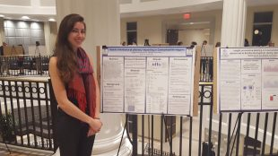Hope Kramer, standing beside her research posters