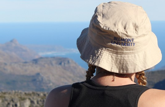 """student wearing a """"Belmont University"""" hat, looking out at mountain view"""