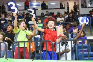 kids cheering from the basketball stands, holding signs with the number 3