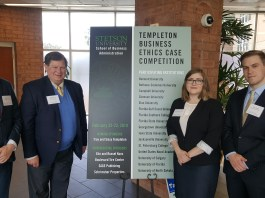the ethics team standing next to a sign for the competition