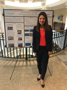 Crystal Lemus, a student, stands in front of her research poster