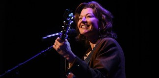 Amy Grant holds her guitar as she stands on stage during chapel at Belmont University.