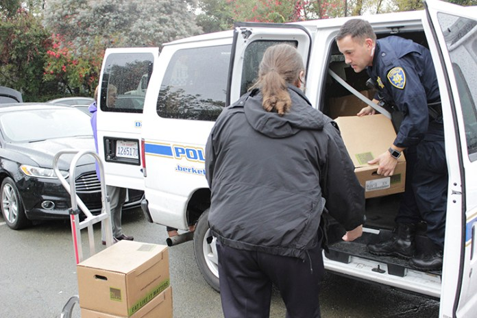 Officer Michael Wyckoff is seen handing the turkeys out to SPO Supervisor Nicole Miller. (UC Berkeley photo by Jeremy Snowden)