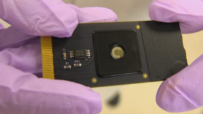 A photo of gloved hands holding an electronic chip