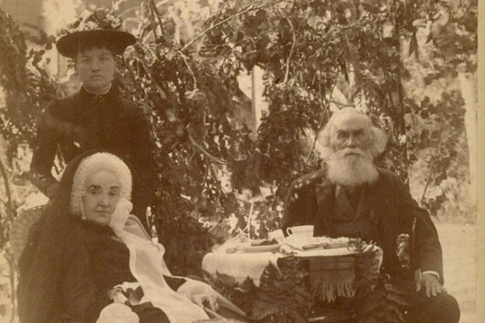 Former UC President John LeConte, shortly before his death in 1891, is seated next to his wife, Eleanor and a caregiver. John LeConte, a physicist, is sporting a thick white beard, balding head and formal dark three-piece suit. His wife is wearing a bonnet, and the caregiver is standing behind the wife in dark dress and hat.