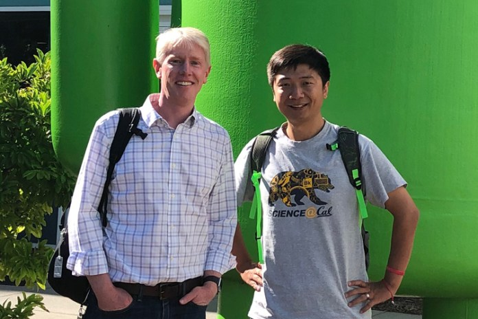 Richard Allen and Qingkai Kong in front of the green Android character at Google