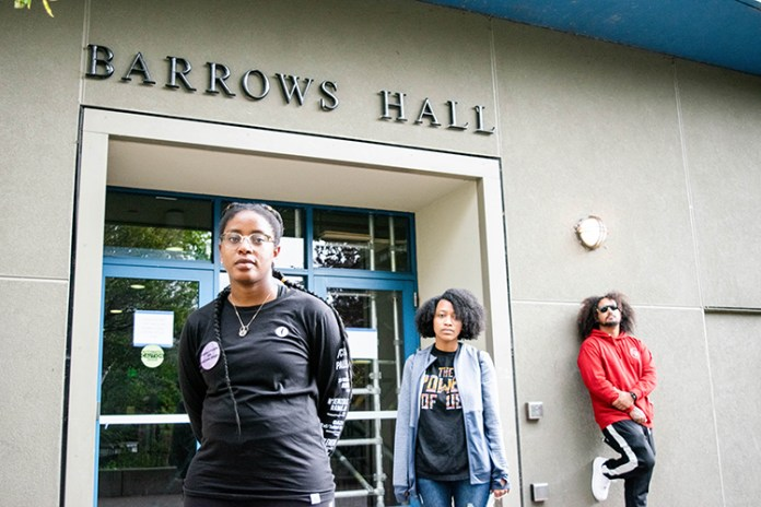 Three African American members of the campus community stand in front of an entrance to Barrows Hall, which was unnamed by campus officials on Nov. 18. Pictured are Melissa Charles, a staff member, Kyra Abrams, a student, and Blake Simons, a student.