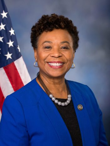 Barbara Lee smiling with American flag in the background