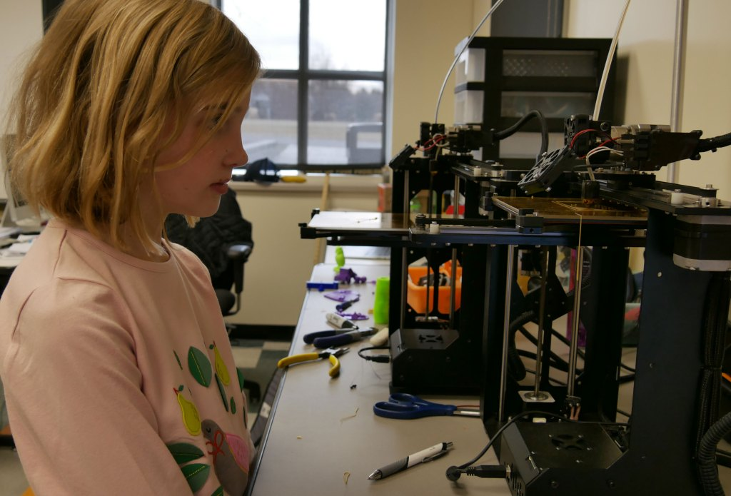 Abby Hollis watches as the 3D printer creates a horse she designed