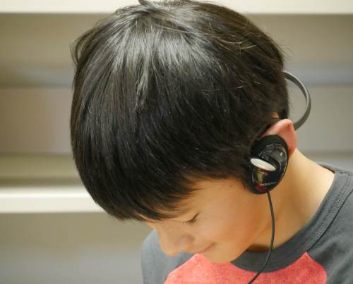 Zander Chao listens to a book on CD while reading it at the same time.
