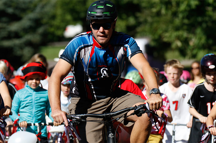 Dr. Mike Davis leads the traditional homecoming bike ride at CA