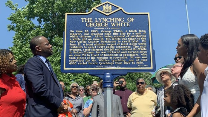A group of people including African Americans gathered around a plaque
