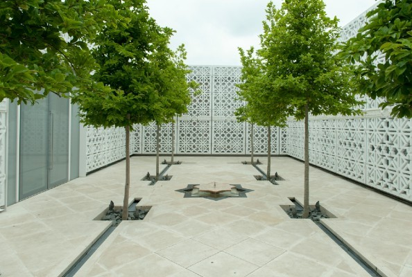 Green trees on mosaic tiled ground surrounding a fountain.