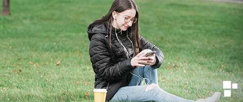 Nichole has long brown hair and wears glasses. Nichole is sitting on some grass and looking at their phone.
