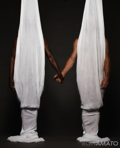 Two men hidden behind curtains holding hands