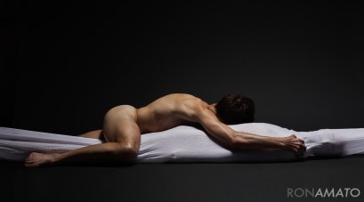 A nude male lies atop a completely shrouded figure
